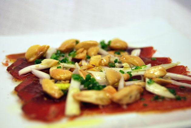 El plato de mojama de Barbate con almendras y cebolleta, una de las originales creaciones del cocinero Carl Borg en Arsenio Manila. Foto: cedida por Arsenio Manila