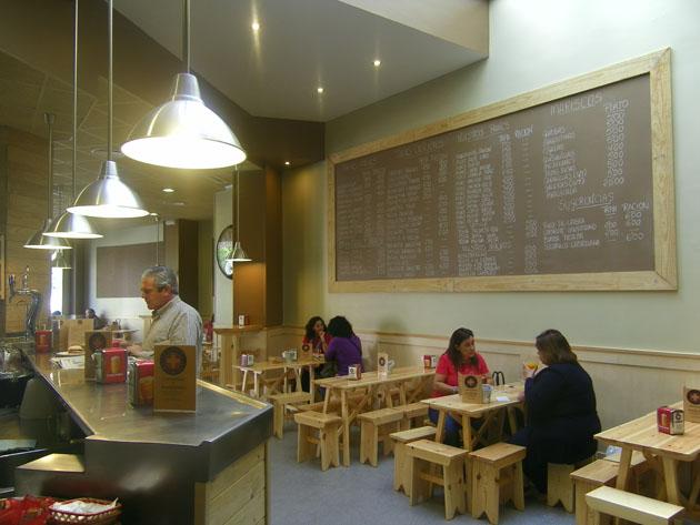Vista del salón del local de la Antigua Cruz Blanca en la plaza del Arenal. Pueden verse las mesas y bancos de madera y la inmensa pizarra donde se anuncian las tapas. Foto: Cosas de Comé.