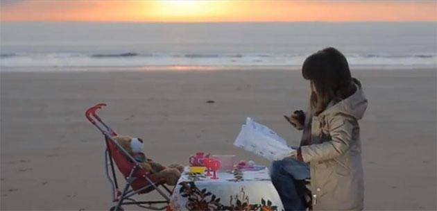 """Imagen del video en el que una niña """"comparte"""" su empanada con su oso de peluche"""